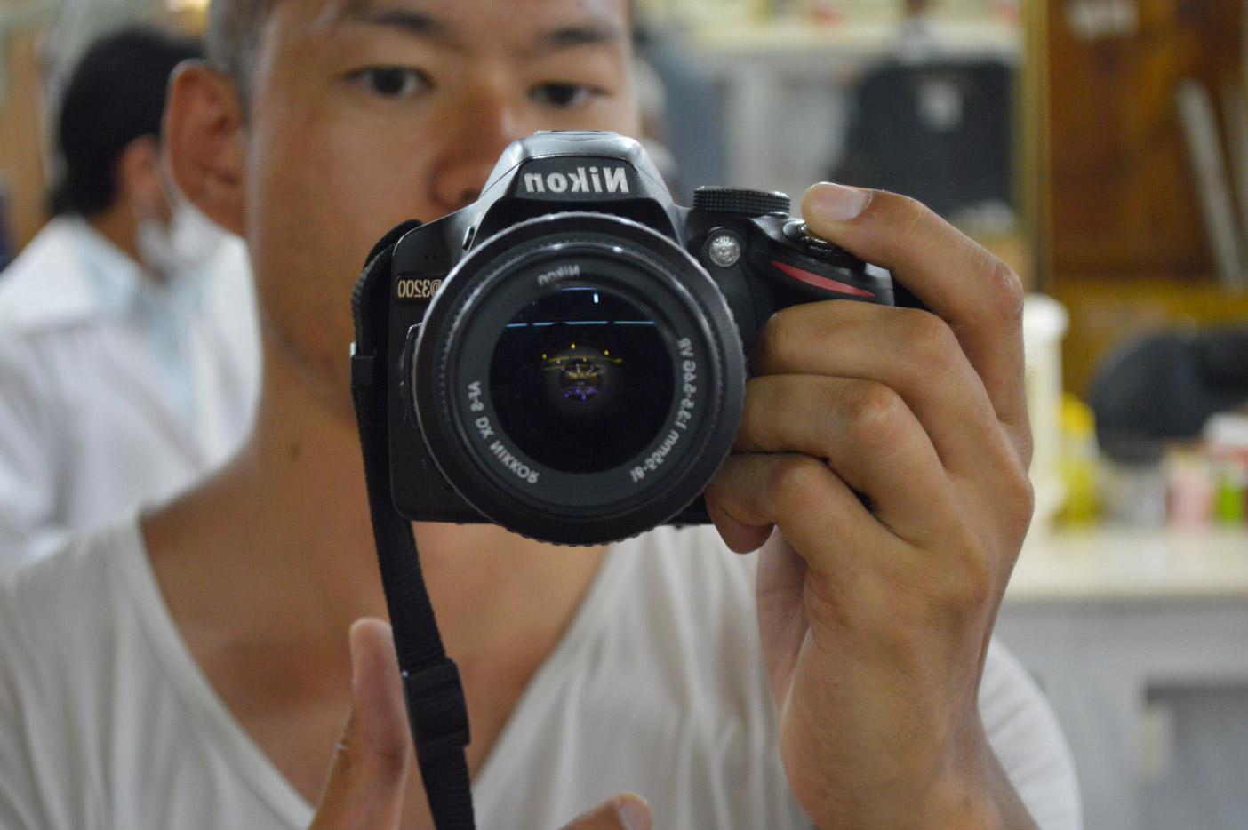 サラーラのバスターミナルスークのサロンでカメラ片手に