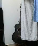 部屋干ししているバスタオルの陰からこちらを窺うギター